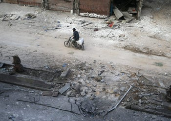 A man rides on a motorbike at a damaged site in the rebel held besieged town of Hamouriyeh, eastern Ghouta, near Damascus, Syria, February 21, 2018