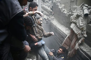 Civil defence help a man from a shelter in the besieged town of Douma in eastern Ghouta in Damascus, Syria, February 22, 2018