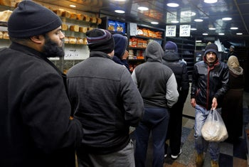 People stand in line to buy bread at a bakery in Amman, Jordan, January 26, 2018.