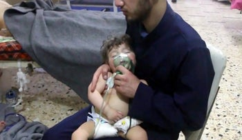 This image made from video released by the White Helmets shows a medical worker giving toddlers oxygen after a gas attack on the rebel-held town of Douma, Syria, April 8, 2018.