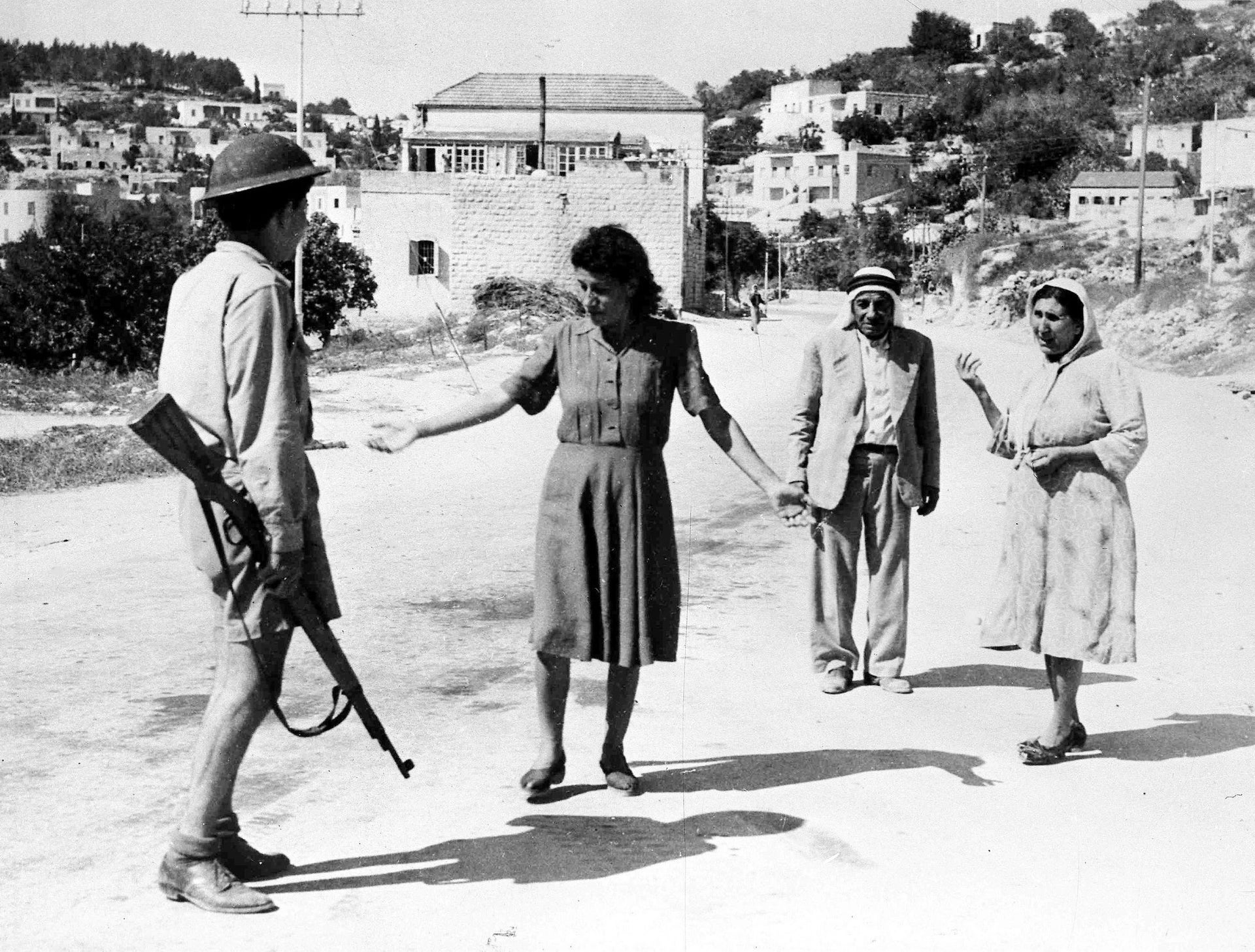 An Israeli soldier stopping some Arabs in a street in Nazareth, July 1948, as they are traveling after the allotted curfew time.