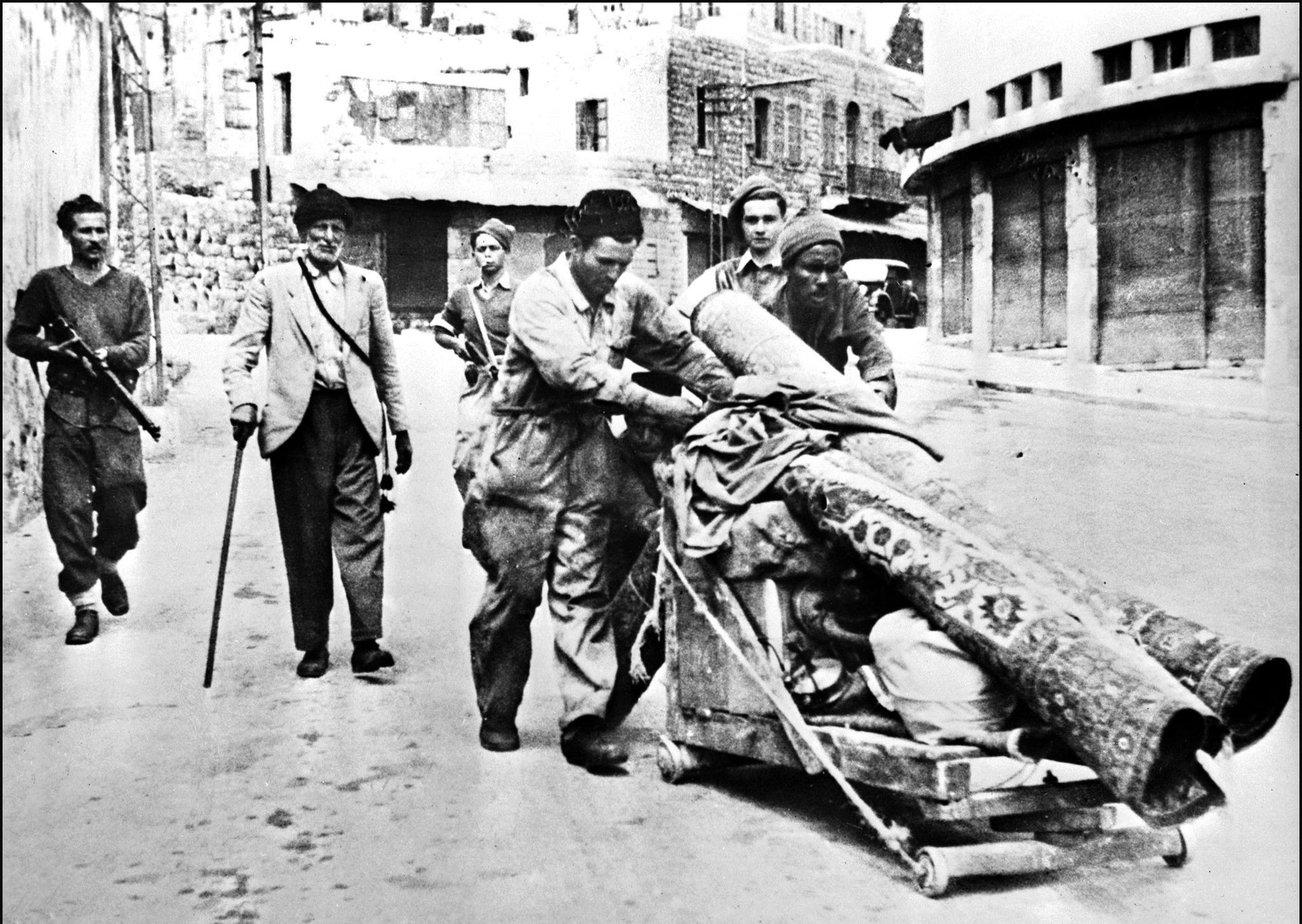Three members of the Haganah (the pre-independence Jewish militia in British Mandatory Palestine) escorting Palestinian Arabs out of Haifa after they were expelled from their homes, May 12, 1948.
