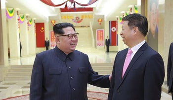 This April 14, 2018 picture released from North Korea's official Korean Central News Agency (KCNA) on April 16, 2018 shows North Korean leader Kim Jong-Un (L) speaking with Song Tao, head of the International Liaison Department of the Central Committee of the Communist Party of China (C), who led the Chinese art troupe in Pyongyang