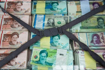 A briefcase filled with Iranian rial banknotes sits on display at a currency exchange market on Ferdowsi street in Tehran, Iran, on Saturday, Jan. 6, 2018. A wave of bad loans from unregulated lenders has rocked the banking sector and oil prices have averaged less than $60 a barrel for the past three years, draining Iran of a key source of revenue. Photographer: Ali Mohammadi/Bloomberg