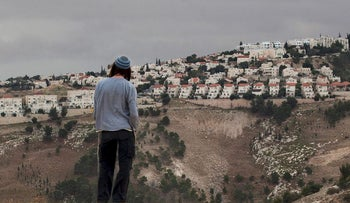 In this Dec. 5, 2012 file photo, a Jewish settler looks at the West bank settlement of Maaleh Adumim, from the E-1 area on the eastern outskirts of Jerusalem