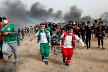 Palestinian medics evacuate a wounded protester during clashes with Israeli forces on April 20, 2018, east of Gaza City.