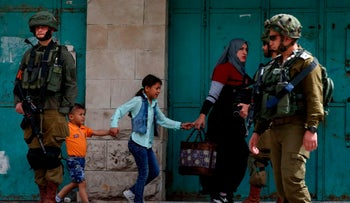 A Palestinian mother and her children walk past Israeli soldiers during clashes with Israeli soldiers in Hebron on April 20, 2018