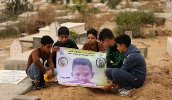 Friends of 15-year-old Palestinian Mohammed Ibrahim Ayoub, who was shot and killed by Israeli security forces during clashes along the Israel-Gaza border, hold up a poster of his portrait by his grave in a cemetery in Beit Lahia in the northern Gaza strip on April 21, 2018.