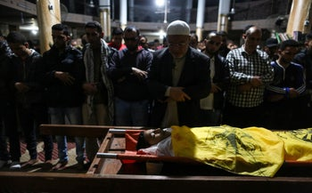 Relatives of 15-year-old Palestinian Mohammed Ibrahim Ayoub pray over his body during his funeral in Beit Lahia in the northern Gaza strip on April 20, 2018