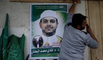 A man hangs a poster depicting Palestinian electrical engineer Fadi al-Batash, who was shot to death in Malaysia, on his family house in the northern Gaza Strip April 21, 2018
