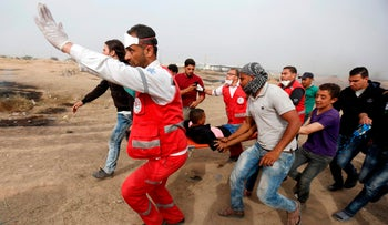 """Palestinian medics evacuate a wounded protester during clashes with Israeli forces on April 20, 2018, east of Gaza City, in the southern Gaza Strip during mass protests along the border of the Palestinian enclave, dubbed """"The Great March of Return,"""" which has the backing of Gaza's Islamist rulers Hamas."""