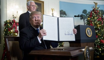 U.S. President Donald Trump holds up a proclamation next to U.S. Vice President Mike Pence, left, after making a statement on Jerusalem in the Diplomatic Room of the White House in Washington, D.C., U.S., on Wednesday, .