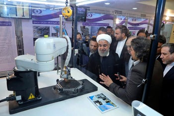 """Iranian President Hassan Rohani listening to explanations on new nuclear achievements at a ceremony to mark """"National Nuclear Day,"""" in Tehran, April 9, 2018."""