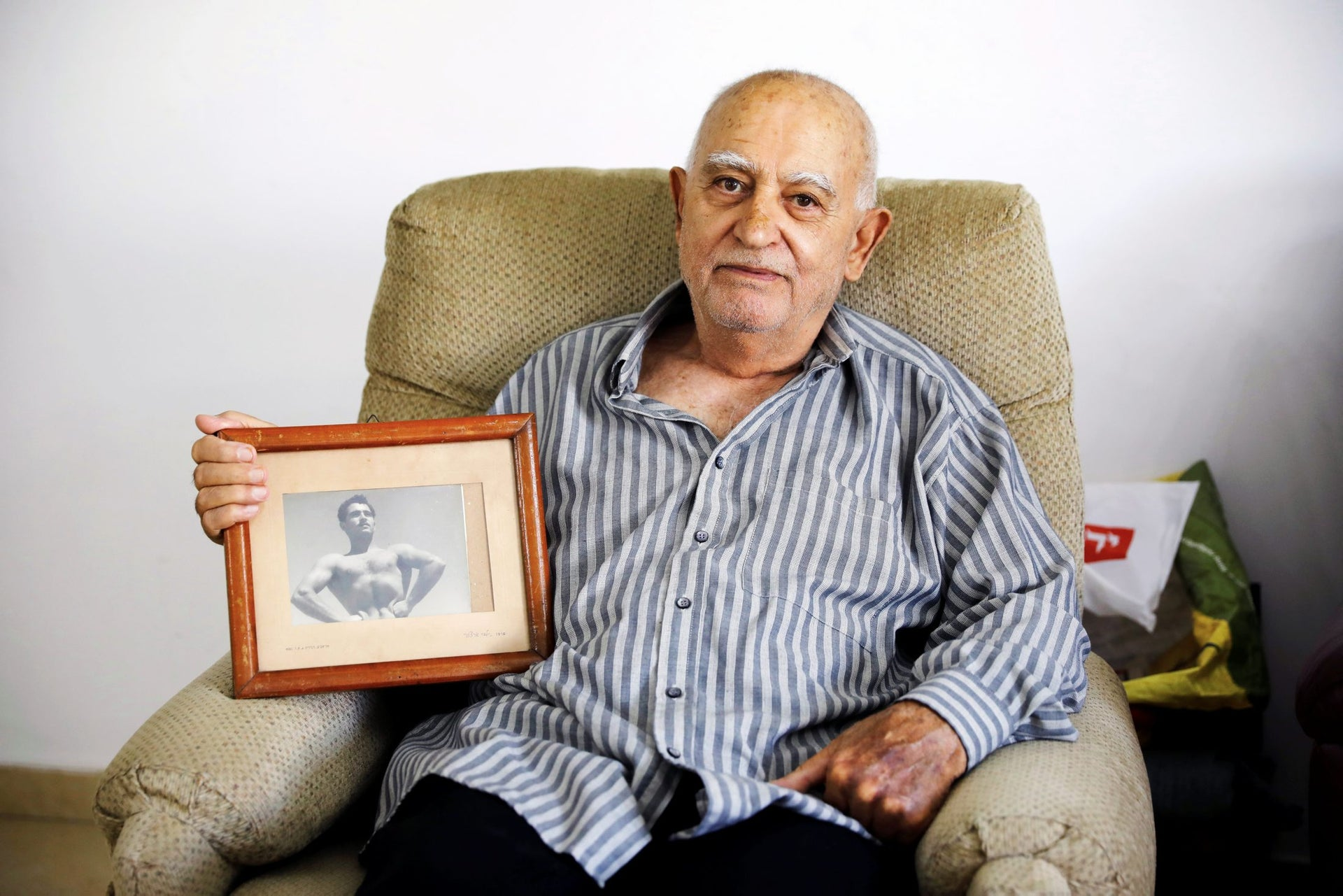 Aharon Ben Hur, 84, who immigrated from Iraq to Israel in 1951, holds an old photo of himself in his house in Rehovot, Israel, April 16, 2018.
