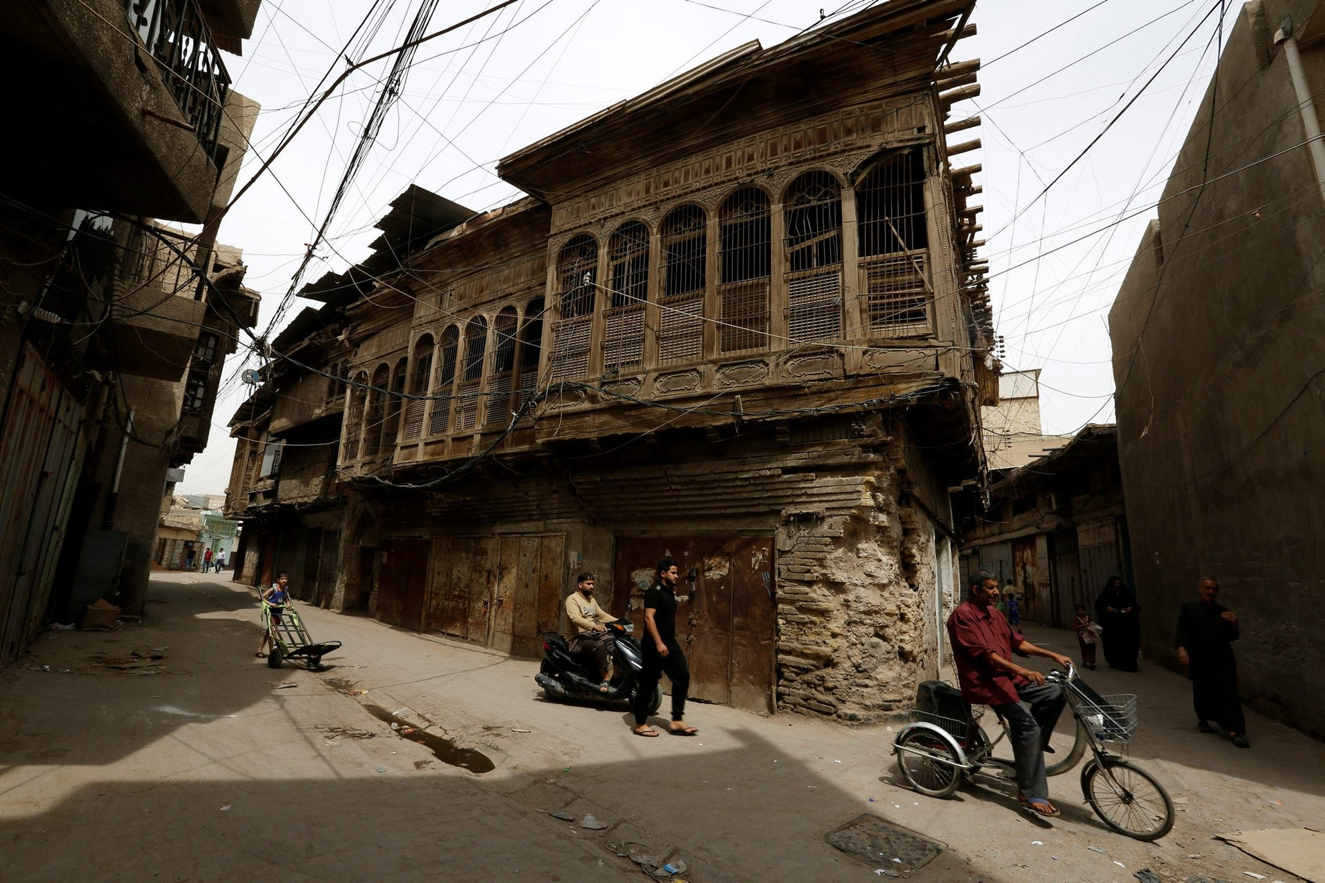 Iraqis pass by old houses in the center of Baghdad, Iraq April 6, 2018.