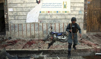 An Afghan police walks outside a voter registration center which was attacked by a suicide bomber in Kabul, Afghanistan, Sunday, April 22, 2018