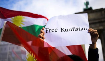 A man shows a poster for a free Kurdistan as he attends a demonstration to support an independent Kurdish state in Berlin, Germany, Friday, Oct. 27, 2017