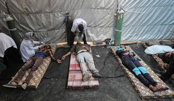 Wounded Palestinians receive treatment at a medical tent, east of Khan Yunis, in the southern Gaza Strip during clashes with Israeli forces on April 20, 2018