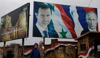 Syrian walk by posters of Syrian President Bashar Assad and Russian President Vladimir Putin in Aleppo, Syria, Thursday, Jan. 18, 2018
