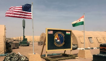 U.S. and Niger flags are raised side by side at the base camp for air forces and other personnel supporting the construction of Niger Air Base 201 in Agadez, Niger, April 16, 2018
