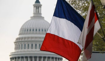 The French flag, along with the American flag and the flag of the District of Columbia, is seen with the U.S. Capitol in the distance in advance of French President Emmanuel Macron's Washington arrival for a state visit, Monday, April 23, 2018.
