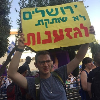 """Andrew Goldbatt at a protest in Israel and holding a sign proclaiming """"Jerusalem will not tolerate racism."""""""