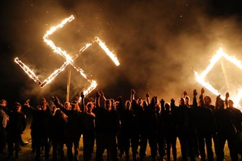 Members of the National Socialist Movement hold a swastika burning after a rally in Draketown, Georgia, on April 21, 2018.