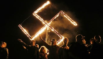 File Photo: Members of the National Socialist Movement hold a swastika burning after a rally in Draketown, Georgia on April 21, 2018.