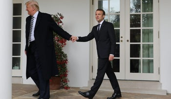 French President Emmanuel Macron (R) and US President Donald Trump (R) walk hand in hand under the colonnades of the White House in Washington, DC, on April 24, 2018. / AFP PHOTO / ludovic MARIN