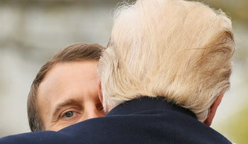 President Donald Trump and French President Emmanuel Macron embrace at the conclusion of a news conference in the East Room of the White House in Washington, Tuesday, April 24, 2018.