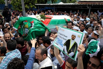 The coffin of Palestinian Fadi al-Batsh is carried out of a mosque after a prayer in Selayang, on the outskirt of Kuala Lumpur, Malaysia, Wednesday, April 25, 2018