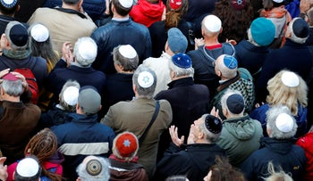 People wear kippas at a demonstration in front of a Jewish synagogue to denounce an anti-Semitic attack last week, Berlin, April 25, 2018.