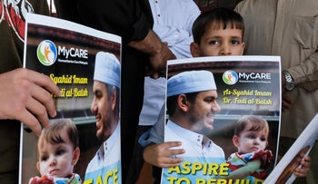 A kid holds a poster of Palestinian Fadi al-Batsh portrait at a mosque in Selayang, on the outskirt of Kuala Lumpur, Malaysia, April 25, 2018.