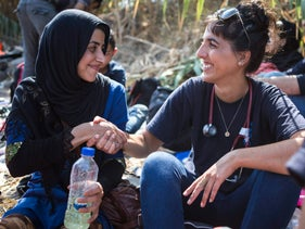 An IsraAID volunteer speaks with a Syrian refugee landing in Lesvos after her boat journey from Turkey