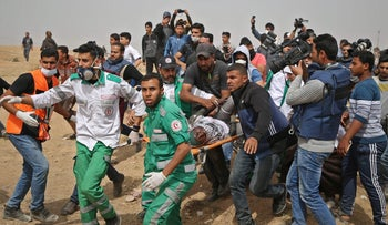 Palestinian paramedics carry away a woman who was injured during clashes with Israeli forces near the Gaza border, April 20, 2018.
