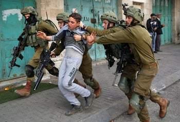 FILE PHOTO: Israeli soldiers detain a Palestinian during clashes at a protest in Hebron in the West Bank, February 23, 2018.