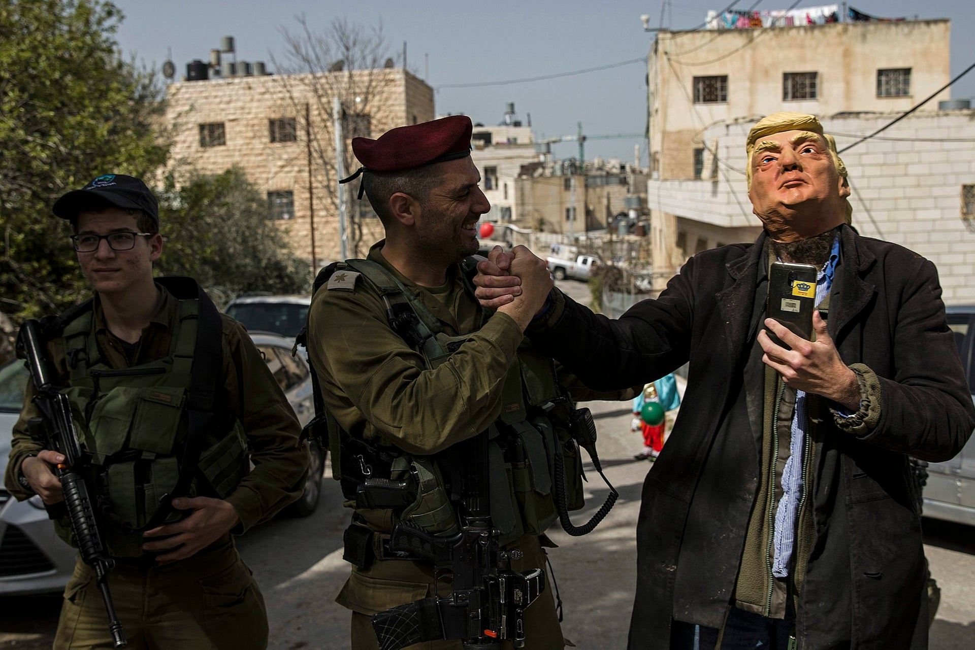 A settler wearing a Trump mask shakes hands with an Israeli soldier as he participates in the annual parade marking the Jewish holiday of Purim, in Hebron, March 1, 2018.