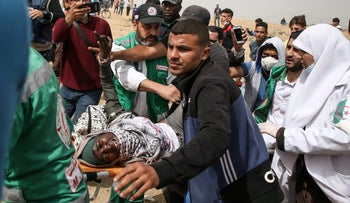 Palestinian paramedics carry away a woman who was injured during clashes with Israeli forces across the Gaza-Israel border, April 20, 2018.