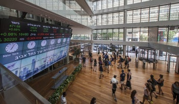 Visitors stand in front of a stock market ticker screen in the lobby of the Tel Aviv Stock Exchange (TASE) in Tel Aviv, Israel, August 4, 2016.