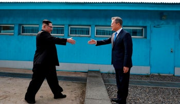 North Korea's leader Kim Jong Un (L) shakes hands with South Korea's President Moon Jae-in (R) at the Military Demarcation Line that divides their countries ahead of their summit at the truce village of Panmunjom on April 27, 2018.