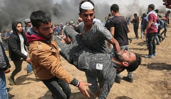 Palestinian demonstrators carry a fellow protestor suffering from tear gas exposure near the southern Gaza Strip town of Khan Yunis during the fifth straight Friday of mass demonstrations and clashes along the Gaza-Israel border on April 27, 2018. / AFP PHOTO / SAID KHATIB