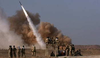 In this photo released by Mehr News Agency, Iranian Revolutionary Guards personnel watch the launch of a Zelzal missile during military maneuvers, Qom, Iran, June 28, 2011.