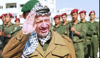 PLO leader Yasser Arafat waves to well wishers as he returns from Cairo to his office in Gaza City, June 12, 1995.