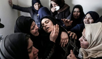 Mourners console the mother (C) of 15-year-old Palestinian teenager Azzam Oweida during his funeral in Khan Yunis in the southern Gaza Strip on April 28, 2018.