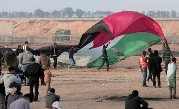 Palestinian protesters wave a large Palestinian flag in front of Israeli soldiers during a protest at the Gaza Strip's border with Israel, east of Khan Younis, Gaza Strip, April 27, 2018.