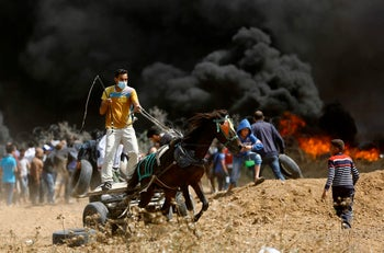 A Palestinian drives a horse-drawn cart during clashes with Israeli security forces near the eastern border of the Gaza Strip, on April 27, 2018