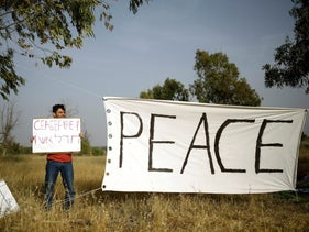 An Israeli peace activist holds a sign in front of the Israel-Gaza border, as Palestinians protest on the Gaza side of the border near Kibbutz Nahal Oz, Israel. April 5, 2018