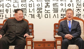 This picture taken on April 27, 2018 and released from North Korea's official Korean Central News Agency (KCNA) on April 29, 2018 shows  North Korea's leader Kim Jong Un (L) talking with South Korea's President Moon Jae-in (R)