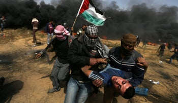 A wounded demonstrator is evacuated during clashes with Israeli troops at a protest, on the Gaza-Israel border, April 27, 2018.