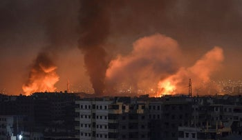 A picture taken late on April 28, 2018 shows smoke plumes rising from explosions in the skyline of a southern district of the Syrian capital Damascus, during regime strikes targeting the Islamic State group in the Palestinian camp of Yarmuk, and neighbouring districts